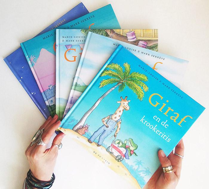 prentenboeken van giraf vastgehouden door handen met ringen