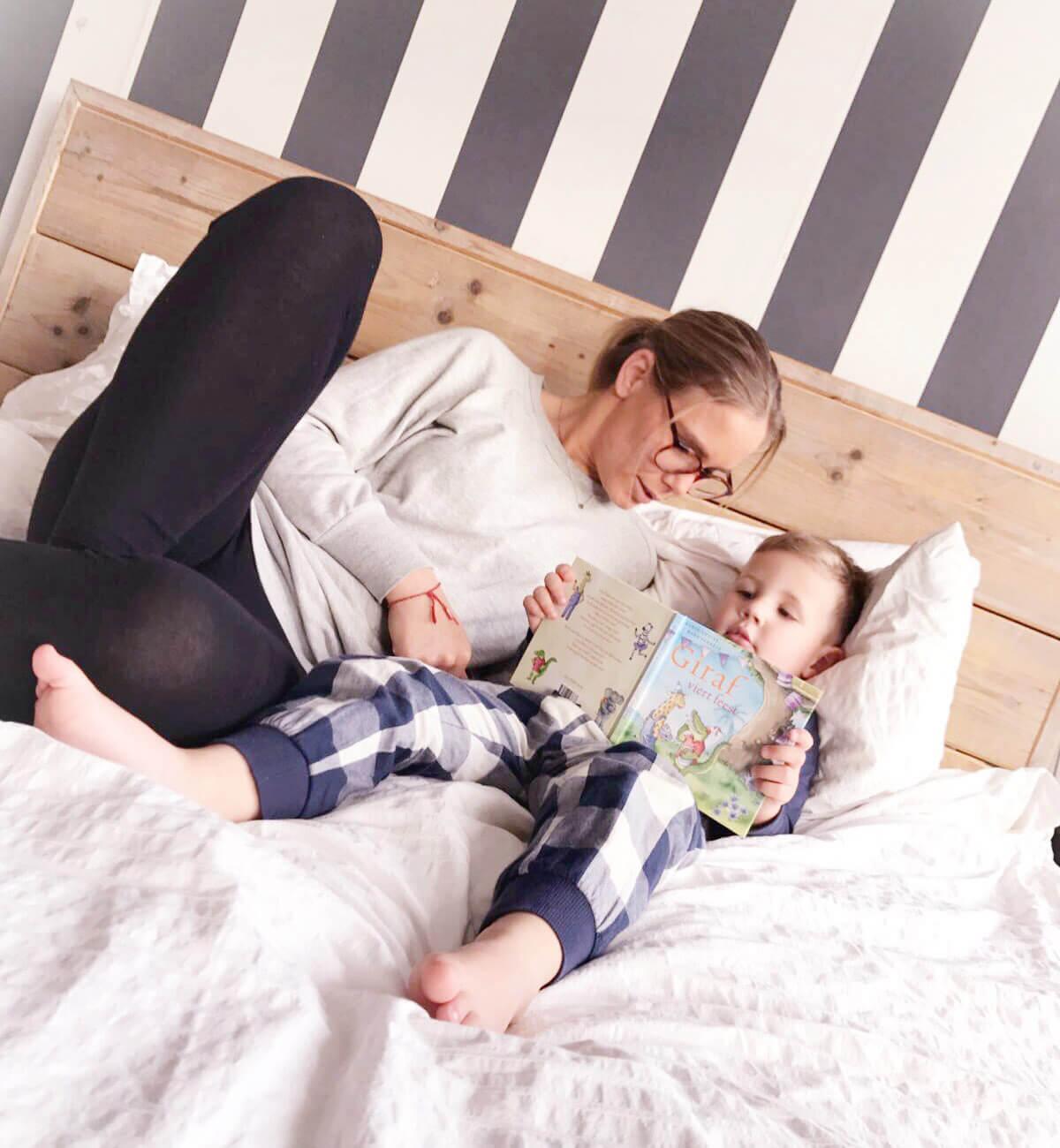 voorlees moeder ligt op bed met haar zoon en leest voor uit Giraf viert feest, reviews prentenboeken, kinderboeken