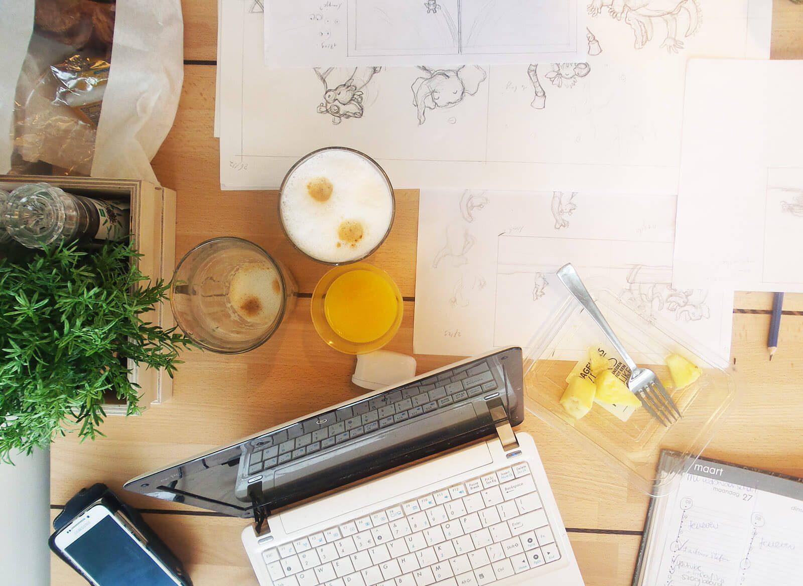 flatlay illustreren giraf gaat logeren laptop en tekeningen op bureau
